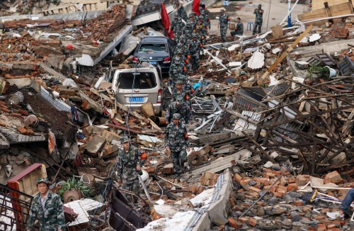 Rescuers search for survivors as they walk among debris of collapsed buildings after an earthquake hit Longtoushan township of Ludian county
